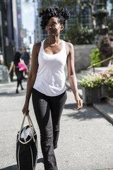 USA, New York City, Manhattan, smiling woman with shopping bag - GIOF02541