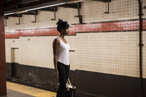 USA, New York City, Manhattan, woman with shopping bag waiting at subway station platform - GIOF02544