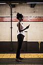 USA, New York City, Manhattan, woman waiting at subway station platform - GIOF02547
