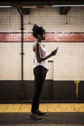 USA, New York City, Manhattan, woman waiting at subway station platform - GIOF02547