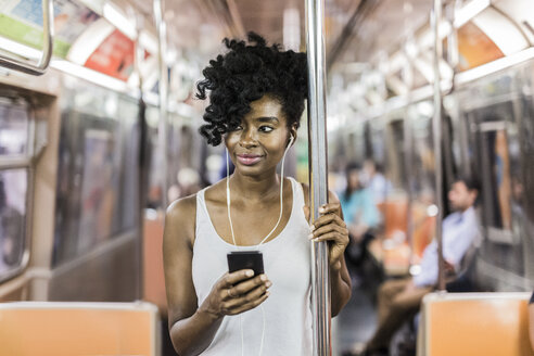 USA, New York City, Manhattan, portrait of relaxed woman with cell phone in underground train - GIOF02550