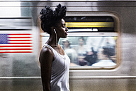 USA, New York City, Manhattan, woman with earphones on subway station platform - GIOF02556