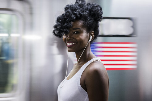 USA, New York City, Manhattan, portrait of happy woman with earphones on subway station platform - GIOF02559