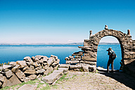 Peru, Titicaca lake, Taquile island, man taking photos of the lake - GEMF01551