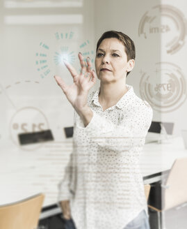 Businesswoman touching glass pane with data in office - UUF10235