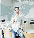 Confident businesswoman looking at glass pane with world map and global network in office - UUF10238