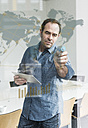 Businessman with tablet touching glass pane with world map and global network in office - UUF10241