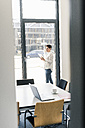 Businesswoman using tablet at the window - UUF10283