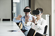 Businessman and businesswoman wearing VR glasses in office - UUF10286