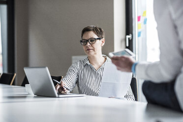 Businesswoman and businessman working in conference room - UUF10289
