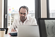 Businessman with earbuds working at desk in office - UUF10295