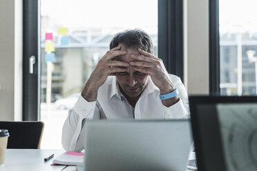 Exhausted businessman sitting at desk in office - UUF10298