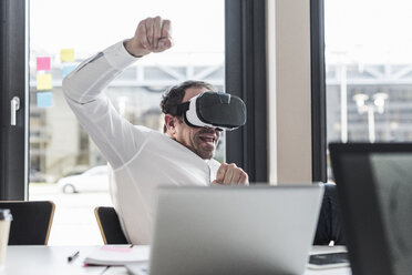 Businessman with VR glasses at desk in office - UUF10301