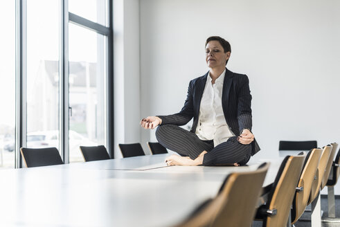 Businesswoman sitting on conference table meditating - UUF10304