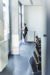 Businesswoman looking out of office window - UUF10307