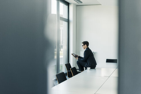 Businesswoman sitting on conference table using tablet - UUF10310