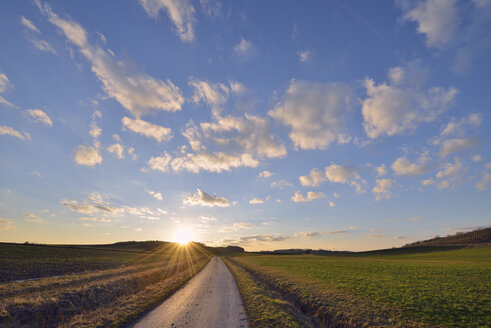 Germany, Bavaria, Sunset with small rural road through fields - RUEF01765