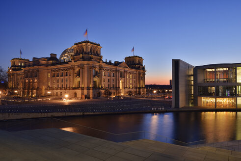 Germany, Berlin, Reichstag and Paul Loebe Government Building at Spree river in the evening - RUEF01774