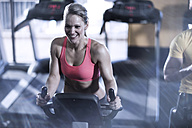 Smiling woman on spinning bike in gym - ZEF13323