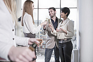 Couple and friends having champagne in open plan apartment with city view - ZEF13350
