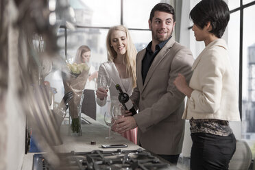 Man with female friends and wine bottle in kitchen - ZEF13359