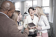 Happy woman showing tablet to friends with champagne glasses at home - ZEF13365