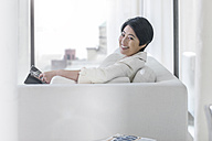 Portrait of smiling young woman on couch with book - ZEF13368