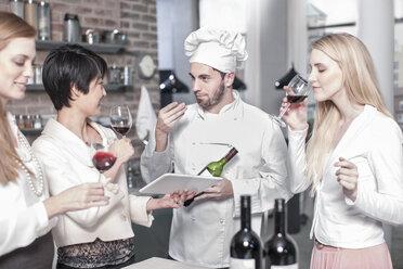 Chef with three women tasting red wine in kitchen - ZEF13371
