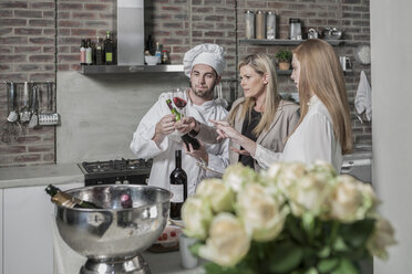 Chef with two women in kitchen tasting wine - ZEF13374