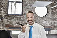 Smiling businessman using cell phone in a loft - FMKF03657