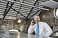 Happy businessman on cell phone sitting at table in a loft - FMKF03660