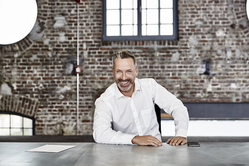 Portrait of happy businessman sitting at table in a loft - FMKF03666