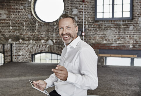 Portrait of happy businessman with tablet in a loft - FMKF03669
