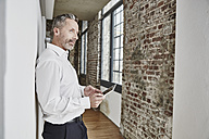 Businessman holding tablet on modern office floor - FMKF03681