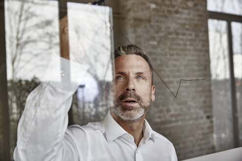 Businessman drawing on glass pane - FMKF03684