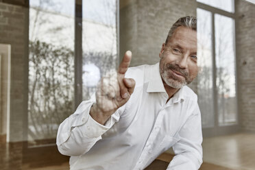 Smiling businessman pointing on glass pane - FMKF03687