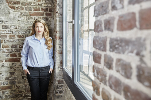 Portrait of confident businesswoman at brick wall - FMKF03690