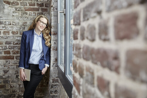 Smiling businesswoman leaning against brick wall holding tablet - FMKF03696
