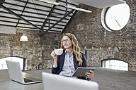 Businesswoman with cup of coffee and tablet at table in a loft - FMKF03702