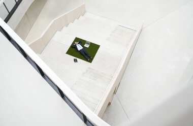 Top view of businesssman lying on stairs next to laptop - FMKF03711
