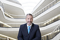 Portrait of confident businessman in modern office building - FMKF03714