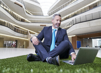 Businesssman sitting on synthetic turf using laptop - FMKF03717