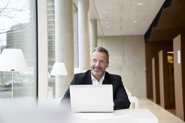 Smiling businesssman using laptop on table - FMKF03723