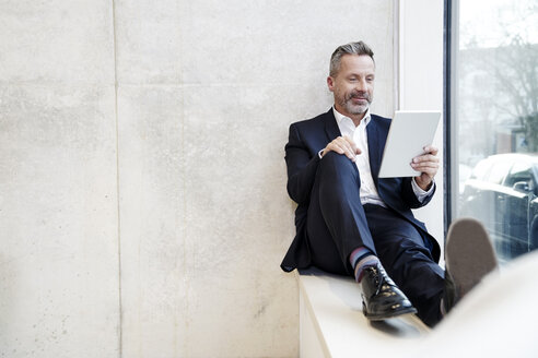Smiling businesssman using tablet at the window - FMKF03729