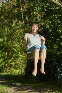 Smiling young woman on swing - JEDF00283