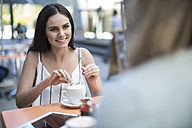 Smiling woman looking at friend at an outdoor cafe - ZEF13395