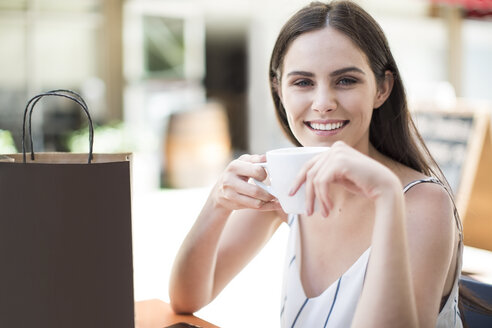 Smiling woman with shopping bag enjoying coffee at cafe - ZEF13398