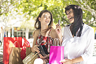 Happy mother and daughter with shopping bags and credit card in the city - ZEF13404