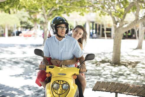 Happy young couple with shopping bags on motor scooter - ZEF13410
