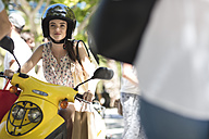 Young woman with shopping bags on motor scooter - ZEF13413